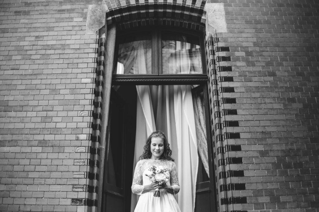 Panna Młoda Patrząca na bukiet po przygotowaniach w koronkowej sukience ślubnej