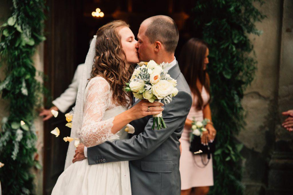 Wyjście z kościoła i całująca się para młoda