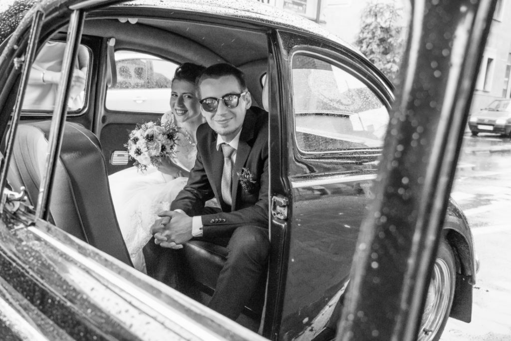 Young couple in the car until the wedding hunchback before the ceremony. Wedding photography. Poznan